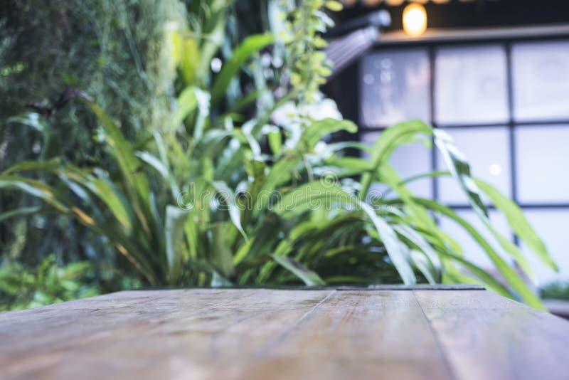 Schließen Sie herauf Bild eines Holztischs mit Unschärfe bokeh der grünen Natur stockbild