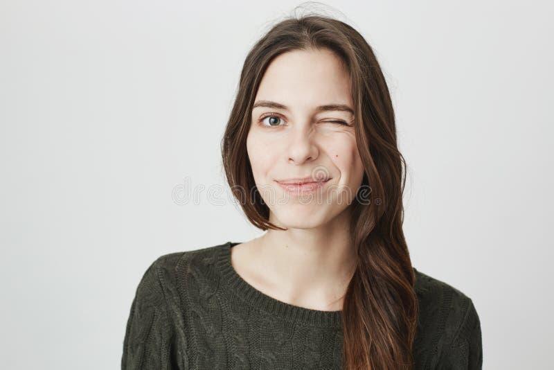 Schließen Sie herauf Bild europäischen Mädchens der Junge des recht in der zufälligen dunkelgrünen Strickjacke blinzelnd und über lizenzfreies stockbild