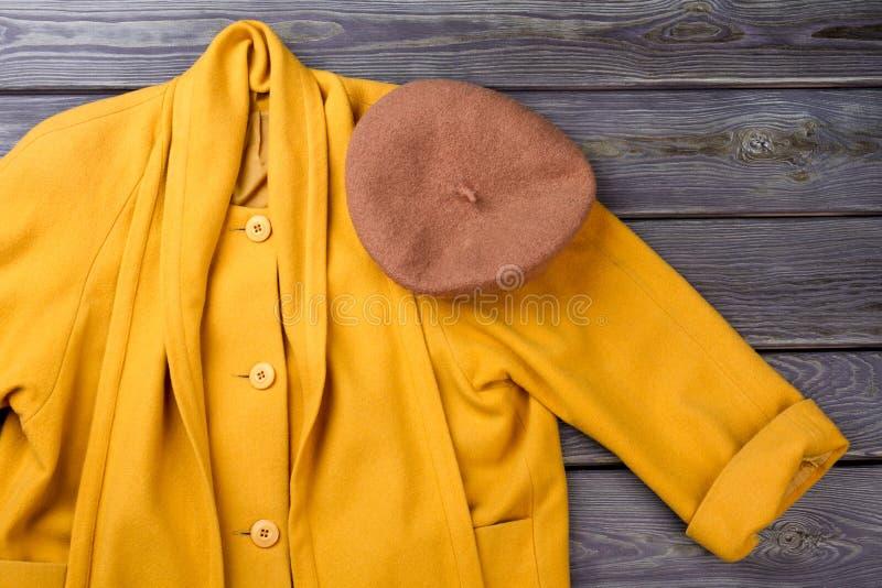 Schließen Sie herauf braunen Baretthut auf gelbem Mantel lizenzfreie stockbilder