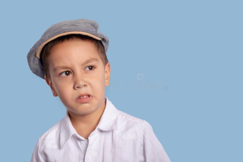 Schließen Sie herauf das emotionale Porträt des Kleinkindes eine Kappe mit tragend stockfotos