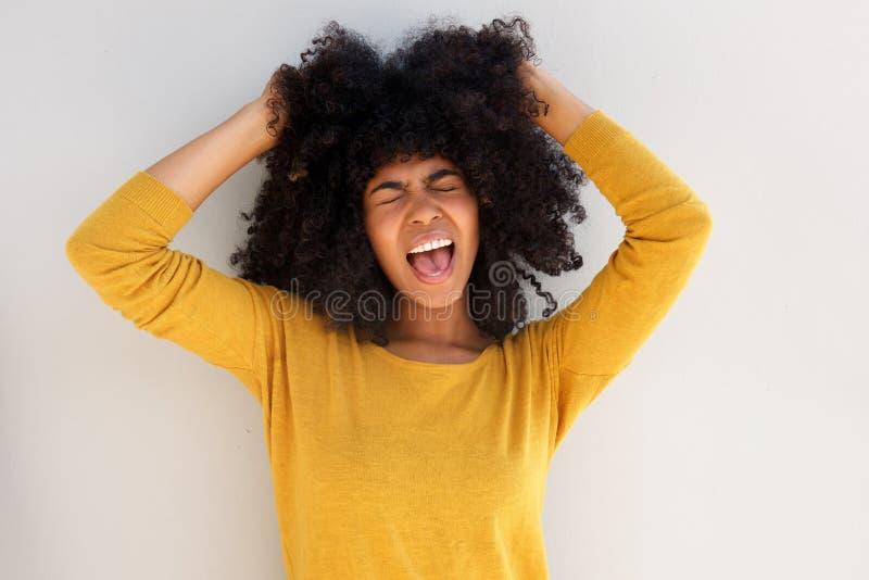 Schließen Sie herauf das junge afrikanische Mädchen, das ihr Haar gegen weißen Hintergrund schreit und zieht lizenzfreie stockfotos