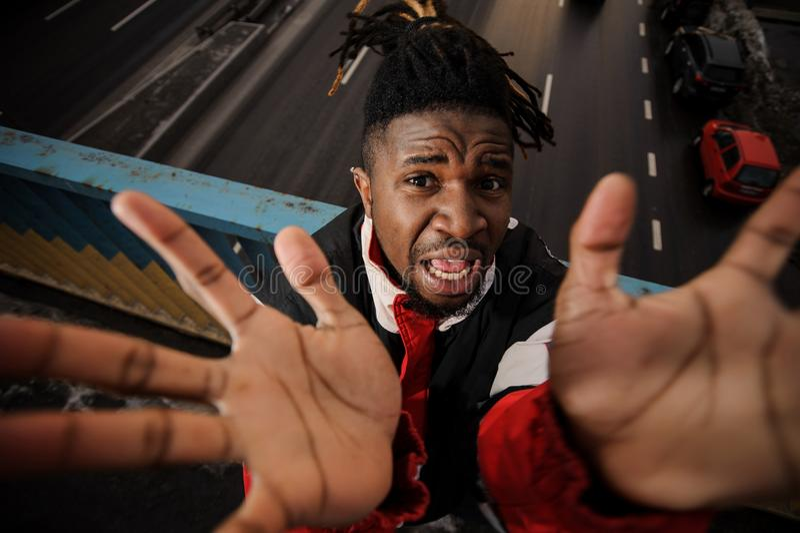 Schließen Sie herauf das portait des Afro-amercan Mannes steigend seine Hände herauf und Störungsbesuch lizenzfreie stockbilder