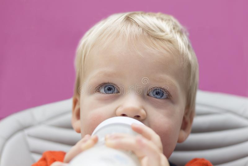 Schließen Sie herauf das Porträt des blauäugigen Kleinkindes seine Flasche trinkend lizenzfreies stockfoto