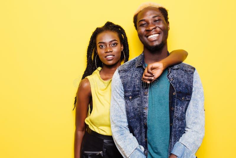 Schließen Sie herauf das Porträt eines reizenden jungen afroen-amerikanisch Paarumarmens lokalisiert auf gelbem Hintergrund lizenzfreie stockfotos