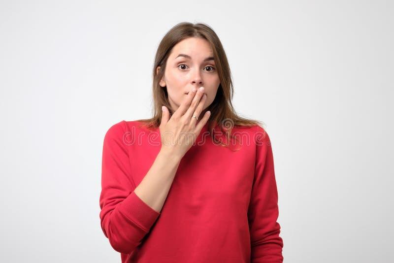 Schließen Sie herauf das Porträt von attraktivem und bezaubern, Frau im roten pulover, das ihren Mund mit den Fingern schließt Si lizenzfreie stockfotografie