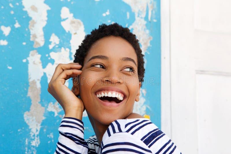 Schließen Sie herauf das schöne junge Afroamerikanerfrauenlachen lizenzfreie stockfotografie