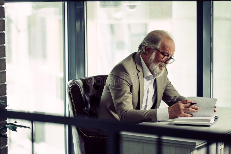 Schließen Sie herauf das Seitenansichtfoto des reifen Geschäftsmannes arbeitend im modernen Büro stockbilder