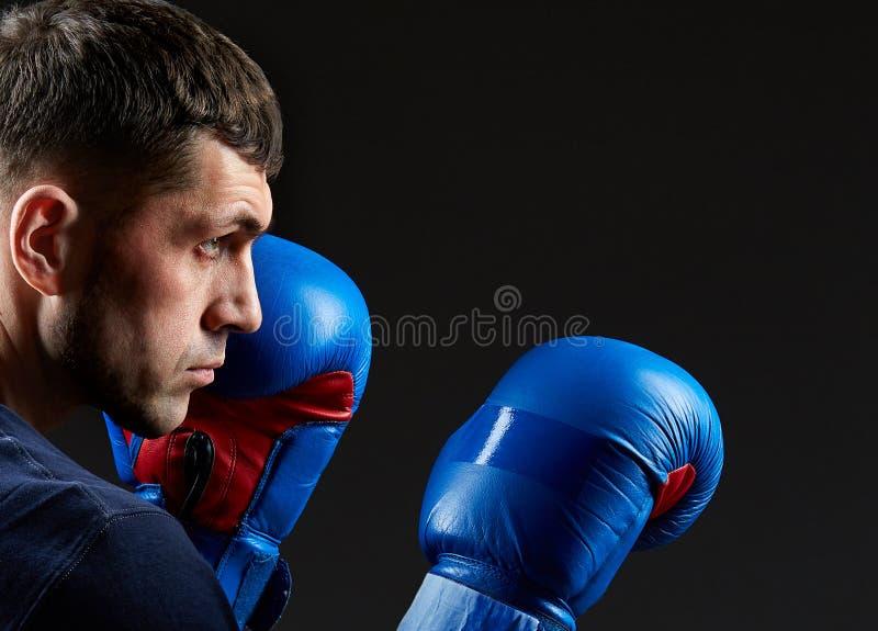 Schließen Sie herauf das zurückhaltende Porträt eines aggressiven muskulösen Kämpfers und seine Faust zeigen, die auf dunklem Hin lizenzfreies stockfoto
