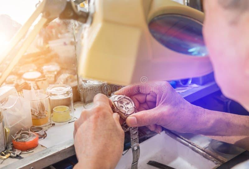 Schließen Sie herauf den Uhrmacher, der alte Uhr des Mechanismus repariert lizenzfreies stockbild