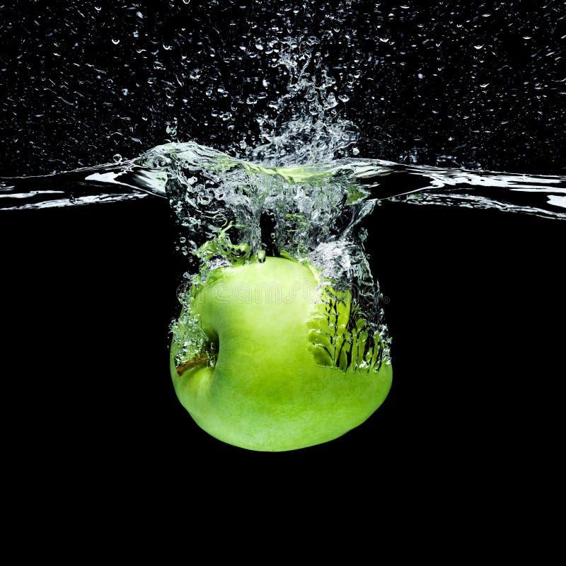 schließen Sie herauf die Ansicht des grünen Apfels fallend in Wasser lizenzfreies stockfoto