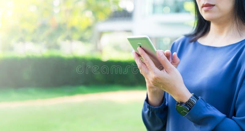Schließen Sie herauf die Asiatin, die Handy außerhalb des Hauses in grünem GA verwendet stockbild