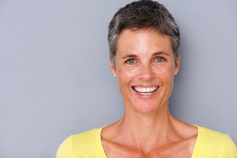 Schließen Sie herauf die attraktive Mittelalterfrau, die gegen grauen Hintergrund lächelt stockbild