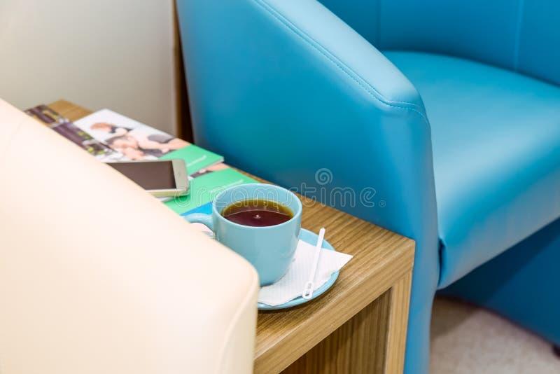 Schließen Sie herauf die Blaue und Elfenbeinstühle und einen Tasse Kaffee auf dem Tisch am Warteraum, Halle Selektiver Fokus stockbilder