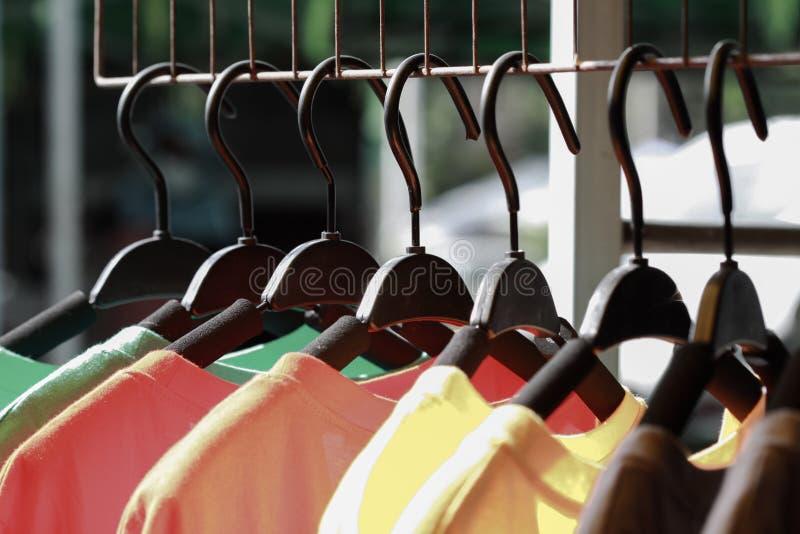 Schließen Sie herauf die bunte hängende Kleidung, buntes T-Shirt auf Aufhängern oder Modekleidung auf Aufhängern stockfotos
