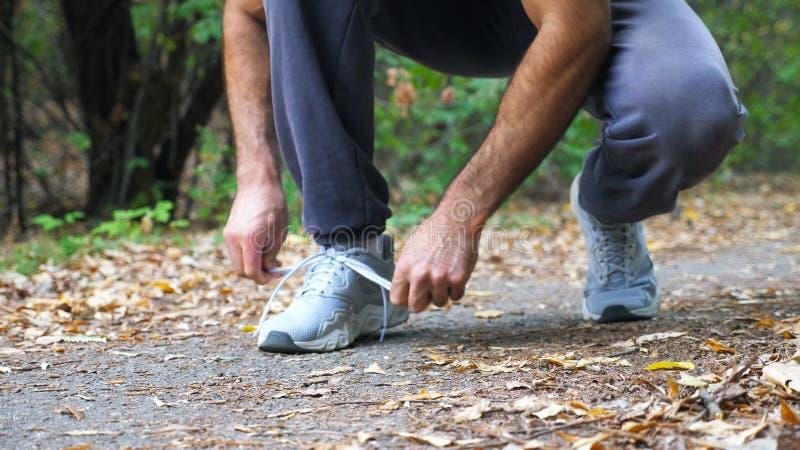 Schließen Sie herauf die Füße des starken Mannes rüttelnd entlang Weg im Frühherbstwaldathleten, der Spitzee auf Turnschuhen währ lizenzfreie stockfotografie