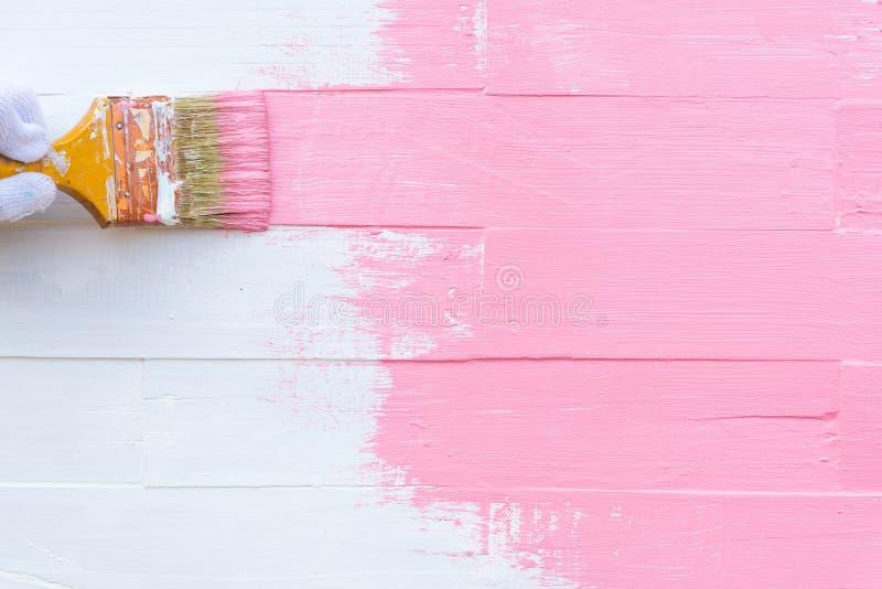 Schließen Sie herauf die Frauenhandholdingbürste, die rosa Farbe malt stockfotografie