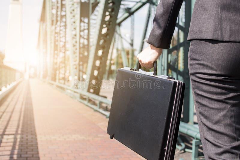 Schließen Sie herauf die Geschäftsfrau, die schwarzen Aktenkoffer auf dem Metall-bri hält lizenzfreies stockfoto