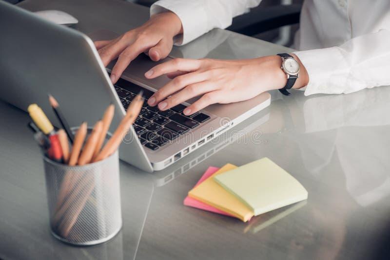 Schließen Sie herauf die Geschäftsfrauhand, die auf Laptop-Computer mit Anmerkung schreibt lizenzfreie stockbilder