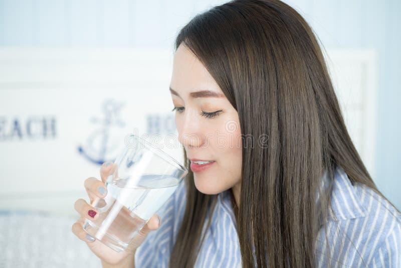 Schließen Sie herauf die gesunde Asiatin, die das Wasser trinkt stockfotos