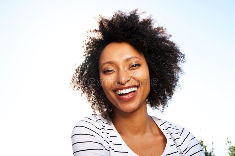 Schließen Sie herauf die glückliche junge schwarze Frau, die draußen gegen hellen Sonnenschein lacht stockbild