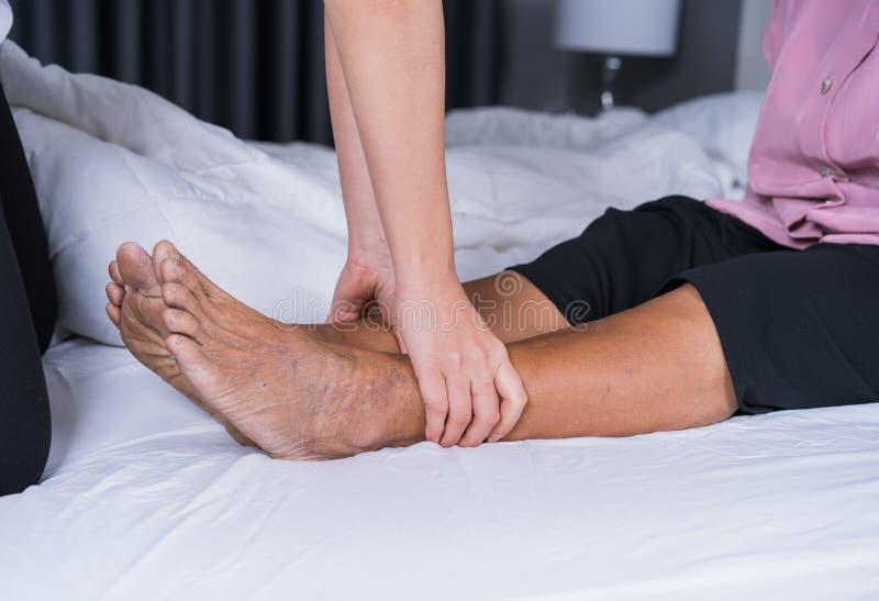 Schließen Sie herauf die Hände, die Massage auf Schmerzbeinen der alten Frau im Bett tun stockfotos