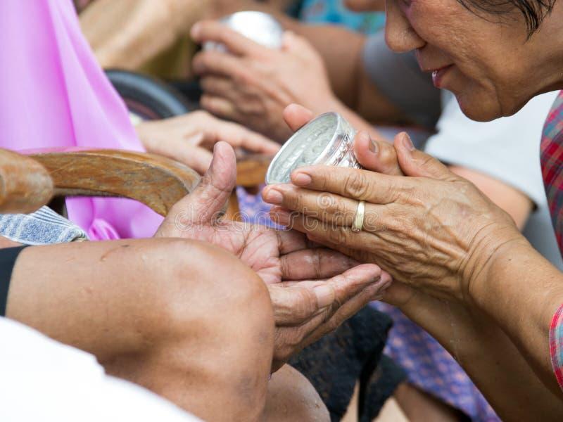 schließen Sie herauf die Hand, die alte Familie für Respekt in Songran-ceremon wässert stockfotos