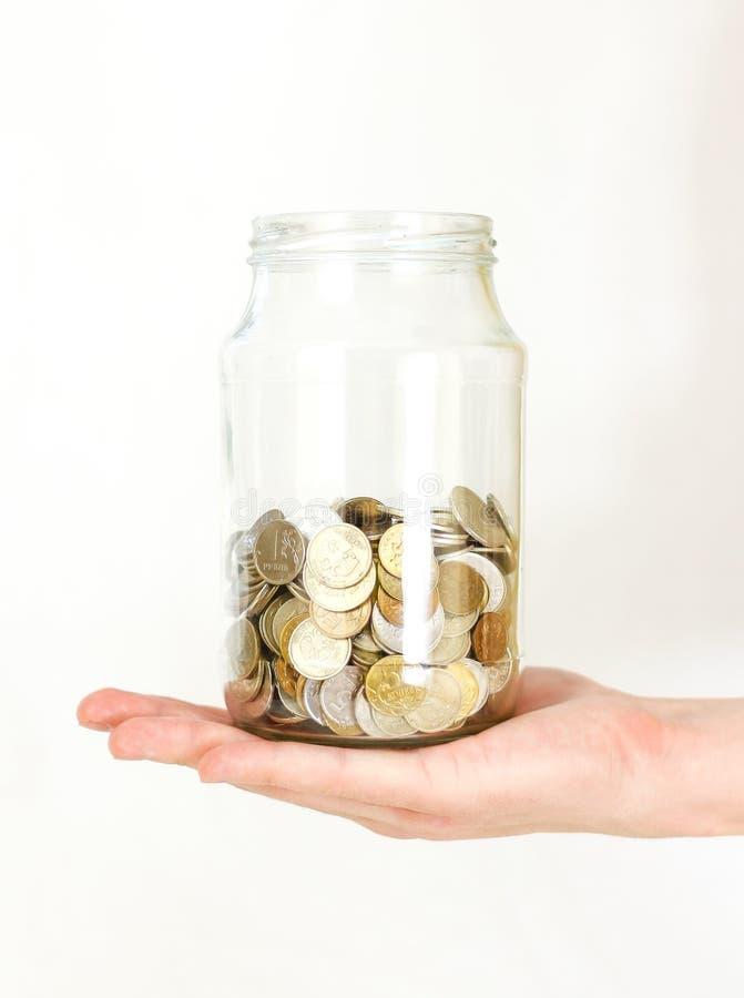 Schließen Sie herauf die Hand, die Münzen im Glasgefäß auf weißer Tabelle hält isolat lizenzfreie stockfotos