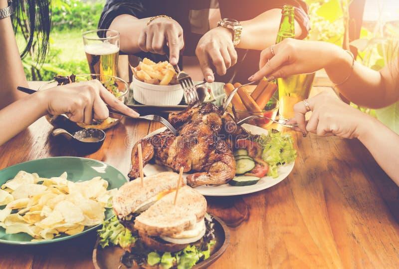 Schließen Sie herauf die Hand und essen Gruppe von Personen, die Konzept, mit Hühnerröstung, Salat, Pommes-Frites auf Holztisch s stockfoto