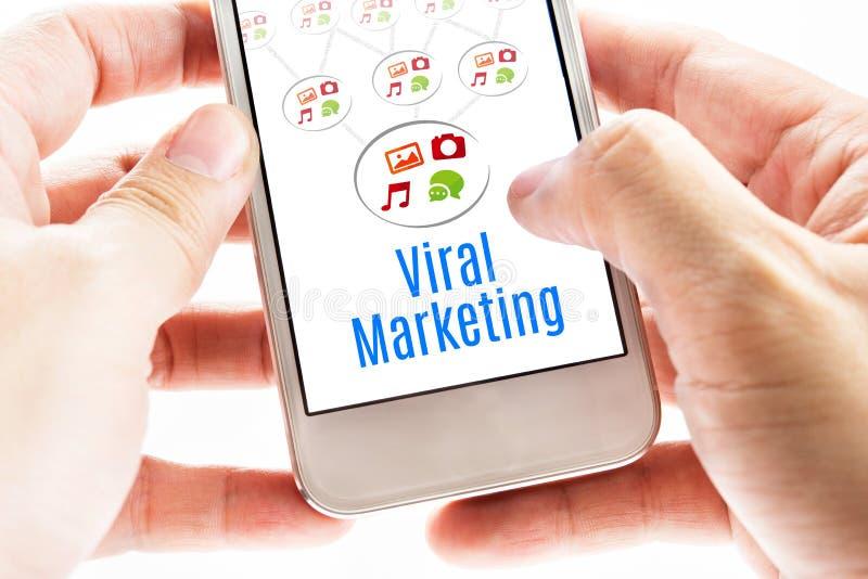 Schließen Sie herauf die Hand zwei, die intelligentes Telefon mit Virenmarketing-Wort hält stockfoto