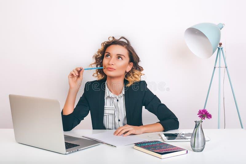 Schließen Sie herauf die junge glückliche Geschäftsfrau des Porträts, die an ihrem Schreibtisch in einem Büro sitzt an einer Lapt stockfotos