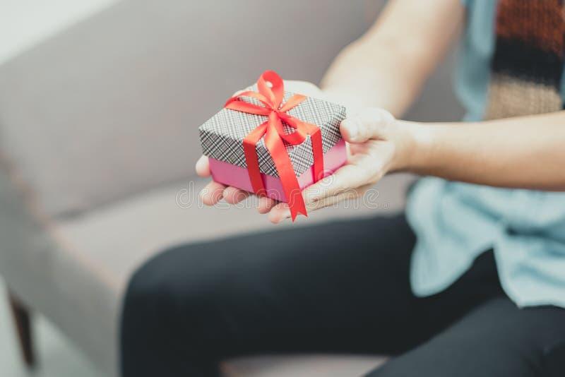 Schließen Sie herauf die männliche Hand, die den Präsentkarton hält, der am Sofa, Geschenk givi sitzt stockfotografie