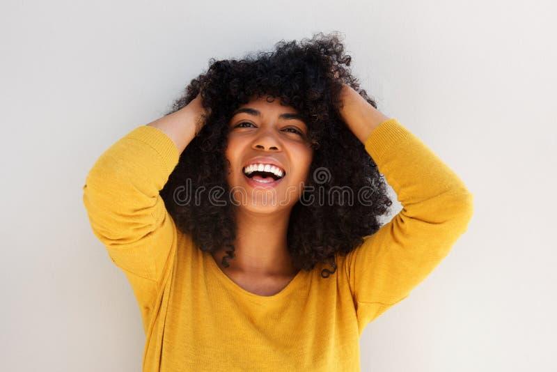 Schließen Sie herauf die nette junge Afroamerikanerfrau, die mit den Händen im gelockten Haar lacht stockfotos