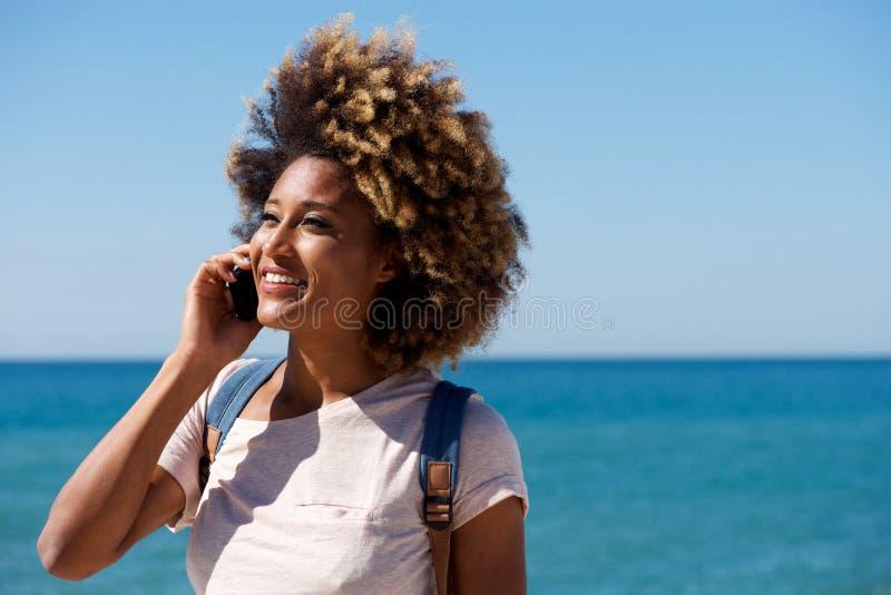 Schließen Sie herauf die schöne afrikanische Frau, die am Handy durch das Meer spricht stockfotos