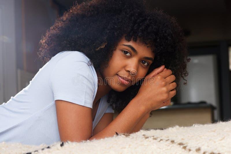 Schließen Sie herauf die schöne afrikanische junge Frau, die auf Boden im Wohnzimmer liegt stockfotografie