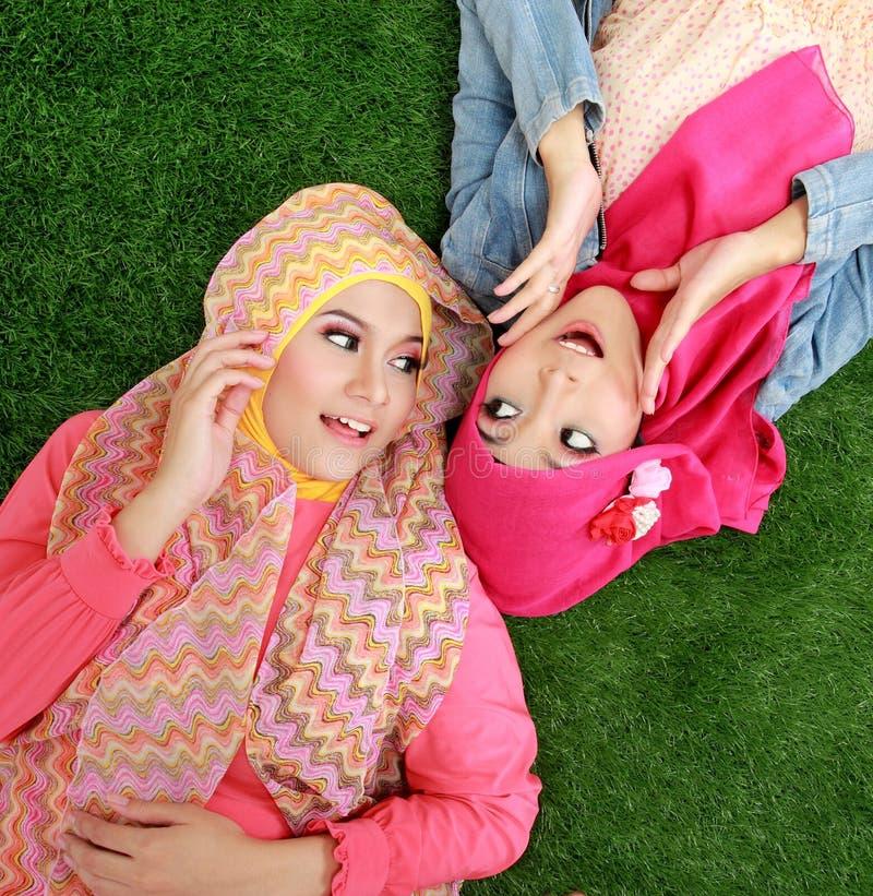 Schließen Sie herauf die schöne glückliche moslemische Frau zwei, die auf Gras liegt stockbild