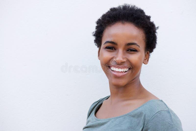 Schließen Sie herauf die schöne junge schwarze Frau, die gegen weißen Hintergrund lächelt lizenzfreies stockfoto
