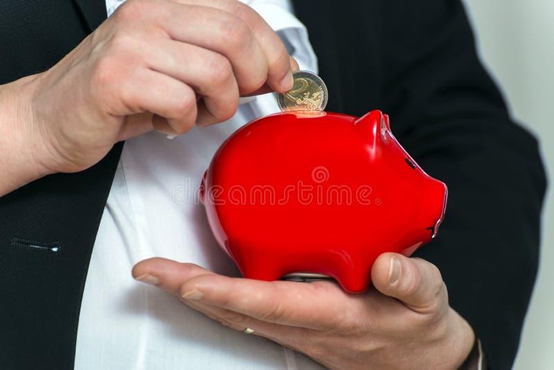 Schließen Sie herauf die schwangeren Hände der Geschäftsfrau mit piggy Querneigung stockfoto