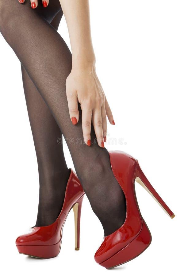 Schließen Sie herauf die sexy Frauen-Beine, die glatte rote Schuhe und Gray Stockings des hohen Absatzes tragen stockbilder
