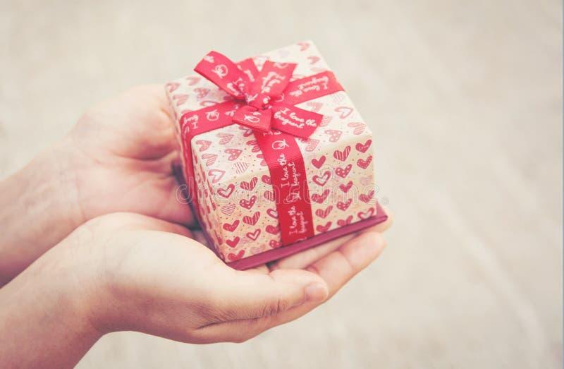 Schließen Sie herauf die weibliche Hand, die ein kleines Geschenkherzmuster hält mit Re lizenzfreies stockfoto