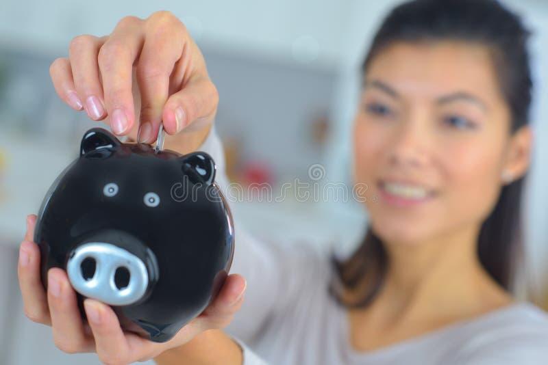 Schließen Sie herauf die weibliche Hand, die Münze in Sparschwein setzt stockfotografie