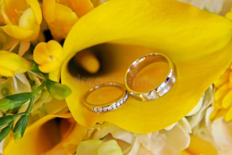 Schließen Sie herauf Eheringe und Blumenstrauß stockbilder