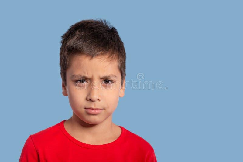 Schließen Sie herauf emotionales Porträt eines Jungen, der ein rotes Hemd mit a trägt stockfoto