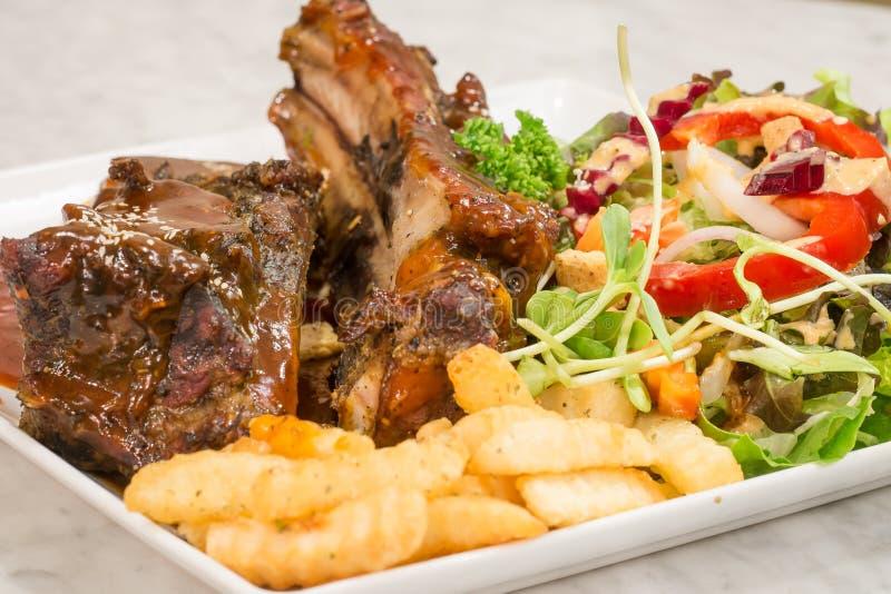 Schließen Sie herauf feinschmeckerisches Hauptgericht mit gegrillter Schweinefleisch-Rippe und Fried Potat stockbild
