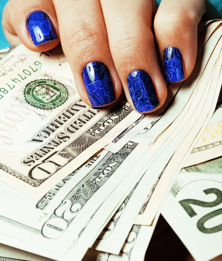 Schließen Sie herauf Finger mit der tiefen blauen kreativen Mustermaniküre, die Dollar hält stockbilder