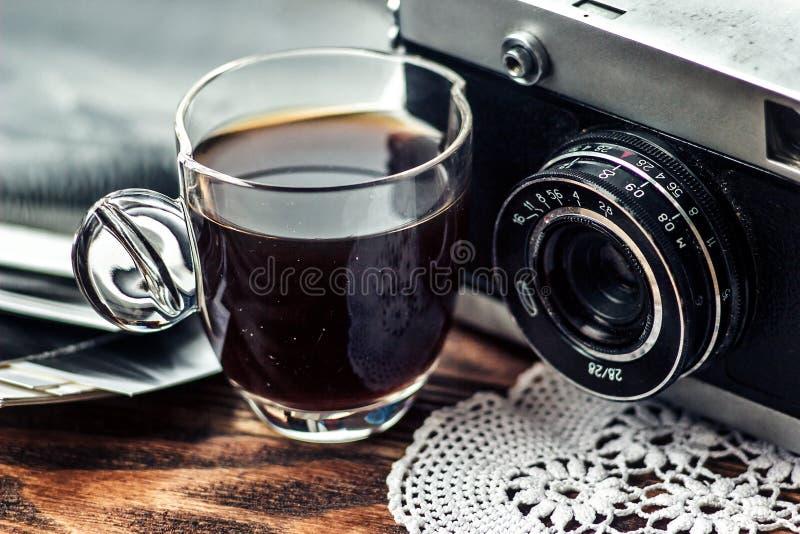 Schließen Sie herauf Foto des altem, WeinleseKameraobjektivs mit Kappe des Kaffees und der Schwarzweiss-Fotos über Holztisch lizenzfreies stockfoto