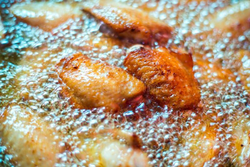 Schließen Sie herauf gebratenes Hühnerflügel in kochendem Öl lizenzfreies stockfoto