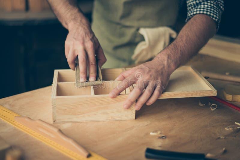 Schließen Sie herauf geerntetes Foto von handicraftsman ` s Händen, die das sur versanden lizenzfreie stockfotos