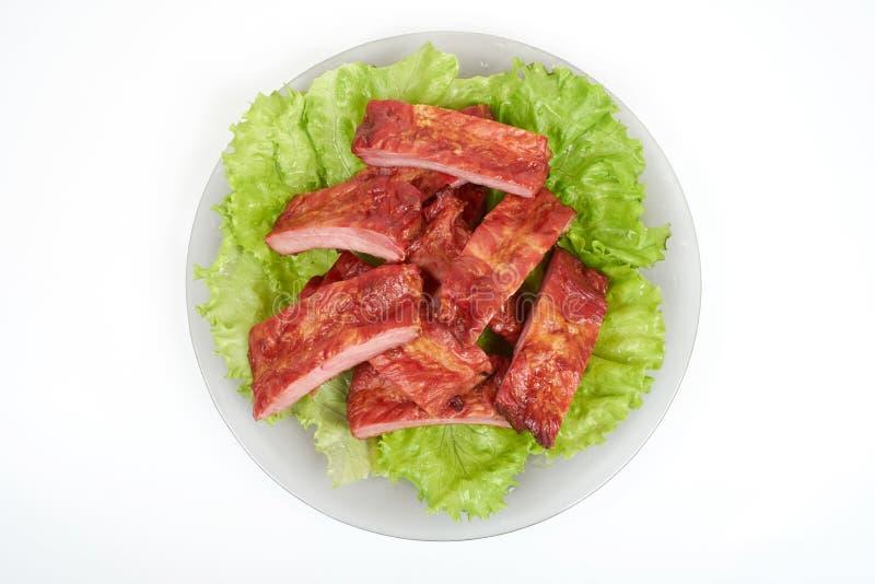 Schließen Sie herauf gegrillte Schweinefleischrippe auf der Platte, die auf weißem Hintergrund lokalisiert wird stockfotografie