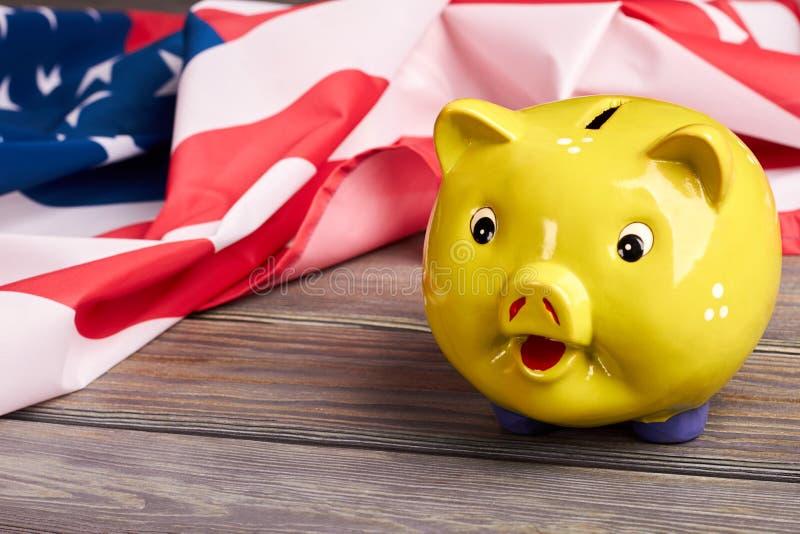 Schließen Sie herauf gelbes Sparschwein und USA-Flagge stockfoto