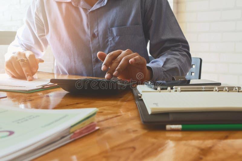 Schließen Sie herauf Geschäftsmannhand unter Verwendung des Taschenrechners lizenzfreie stockbilder